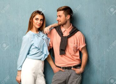Fashion girl and guy in outlet clothes posing on a blue background